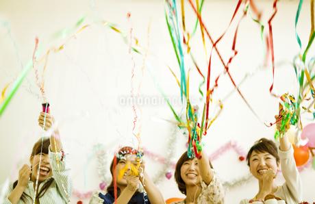 クラッカーを鳴らす若い女性4人の写真素材 [FYI01300463]