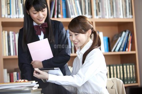 タブレットPCを見て話す先生と学生の写真素材 [FYI01300499]