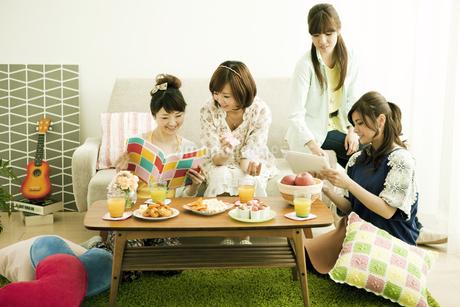 部屋でくつろぐ若い女性4人の写真素材 [FYI01300519]