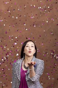 紙吹雪を吹く中高年女性の写真素材 [FYI01300567]