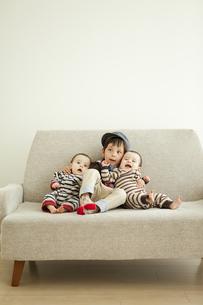 ソファーに座る男の子と双子の赤ちゃんの写真素材 [FYI01300592]