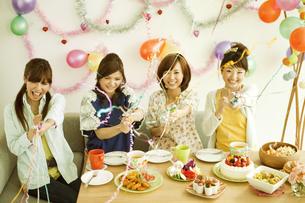 クラッカーを鳴らす若い女性4人の写真素材 [FYI01300624]
