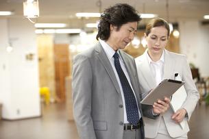 タブレットPCを見ているビジネスマンとビジネスウーマンの写真素材 [FYI01300653]