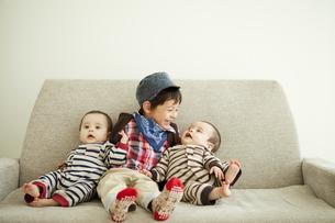 ソファーに座る男の子と双子の赤ちゃんの写真素材 [FYI01300712]