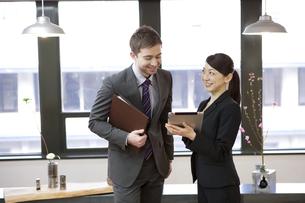 タブレットPCを見て話すビジネスマンとビジネスウーマンの写真素材 [FYI01300714]