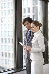 タブレットPCを見ているビジネスマンとビジネスウーマンの写真素材 [FYI01300747]
