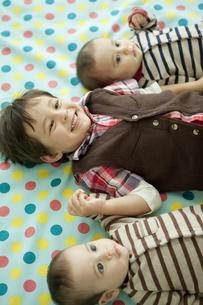 寝転ぶ男の子と双子の赤ちゃんの写真素材 [FYI01300748]