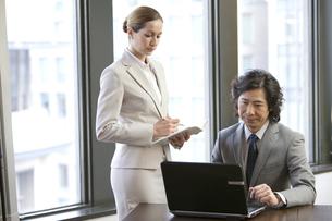 ノートパソコンを見ているビジネスマンとビジネスウーマンの写真素材 [FYI01300749]