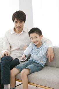 リモコンを操作する男の子と父親の写真素材 [FYI01301093]