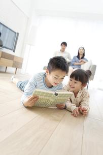 寝転んで本を読む兄と妹の写真素材 [FYI01301151]