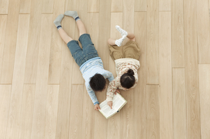 寝転んで本を読む兄と妹の写真素材 [FYI01301163]