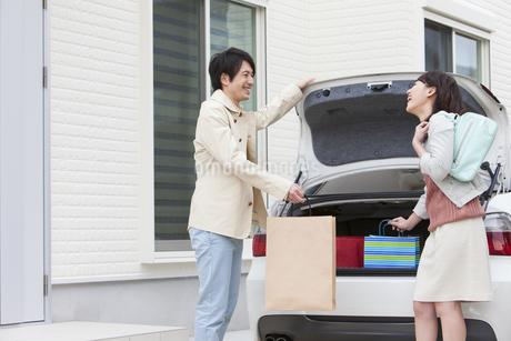 トランクから買い物袋を取り出す夫婦の写真素材 [FYI01301251]