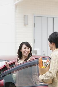 買い物袋を持つ男性と車から降りる女性の写真素材 [FYI01301301]