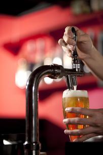 サーバーでビールを注ぐ手の写真素材 [FYI01301314]