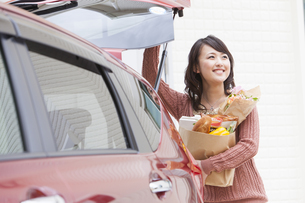 トランクから出した買い物袋を持つ女性の写真素材 [FYI01301356]