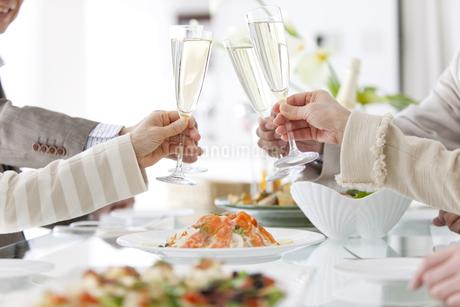 シャンパンで乾杯をする中高年男女4人の写真素材 [FYI01301409]