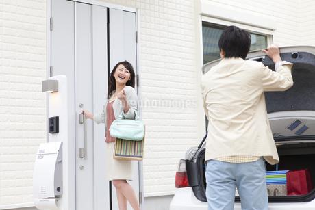 家に入ろうとする女性とトランクを開ける男性の写真素材 [FYI01301415]