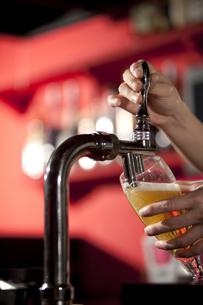サーバーでビールを注ぐ手の写真素材 [FYI01301424]