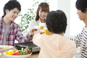 ビールで乾杯している若者4人の写真素材 [FYI01301953]