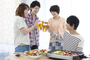 ビールで乾杯している若者4人の写真素材 [FYI01301965]