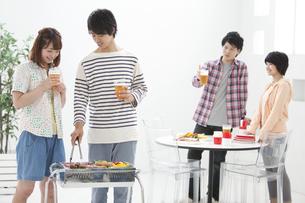 バーベキューをする若者4人の写真素材 [FYI01302027]