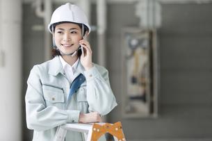 建設現場で電話をするビジネスウーマンの写真素材 [FYI01302210]