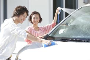 家の前で洗車をする夫婦の写真素材 [FYI01302291]