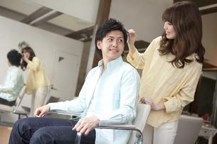 髪をセットする美容師の写真素材 [FYI01302419]