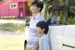 車にもたれる父親と息子の写真素材 [FYI01302488]