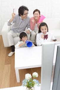 リビングでテレビ観戦する家族4人の写真素材 [FYI01302781]