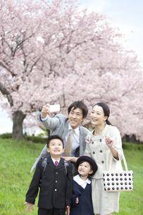 スマートフォンで撮影する4人家族の写真素材 [FYI01302803]