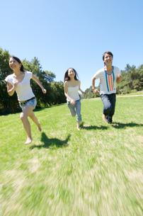 芝生を走る若者3人の写真素材 [FYI01302953]