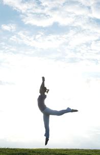 芝生の上でジャンプする女性の写真素材 [FYI01302999]