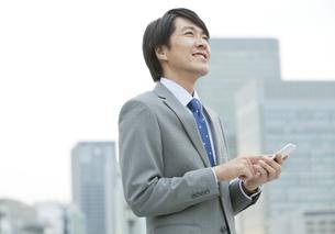 スマートフォンを持つビジネスマンの写真素材 [FYI01303068]