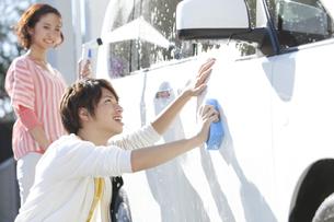 家の前で洗車をする夫婦の写真素材 [FYI01303075]