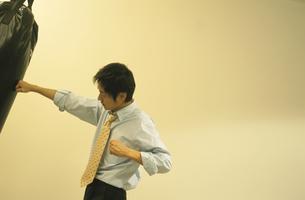 サンドバッグを叩くビジネスマンの写真素材 [FYI01303077]