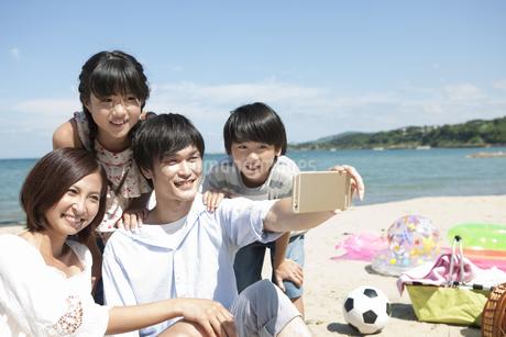 スマートフォンで撮影する4人家族の写真素材 [FYI01303093]