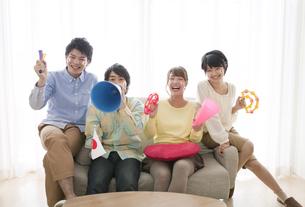 ソファーに座って応援する男女4人の写真素材 [FYI01303160]