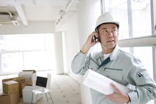建設現場で電話をする男性作業員の写真素材 [FYI01303164]