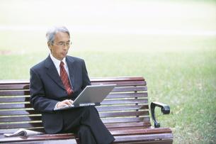 ベンチでノートパソコンをするビジネスマンの写真素材 [FYI01303252]