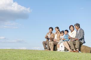 丸太に座っている3世代家族の写真素材 [FYI01303400]