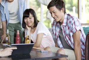 飲食店でドリンクを飲む男女3人の写真素材 [FYI01303439]