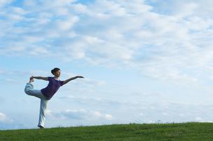 芝生の上でヨガをする女性の写真素材 [FYI01303489]