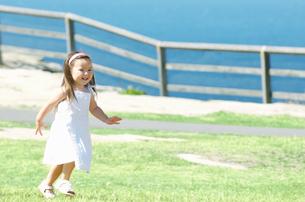 芝生を走る女の子の写真素材 [FYI01303726]