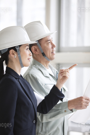 建設現場で打ち合わせをする男女2人の写真素材 [FYI01303759]