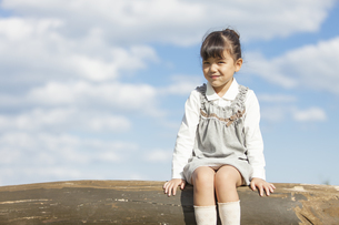 丸太に座っている女の子の写真素材 [FYI01303775]
