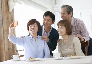 スマートフォンで写真を撮る中高年4人の写真素材 [FYI01303802]
