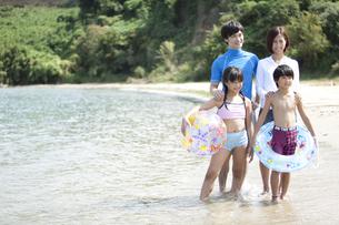 海辺に佇む4人家族の写真素材 [FYI01303834]