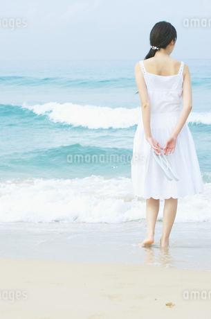 波打ち際に立つ女性の後姿の写真素材 [FYI01303845]