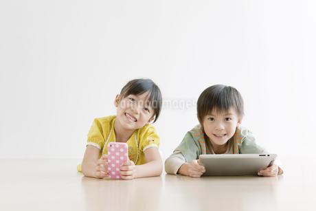 床に寝そべる男の子と女の子の写真素材 [FYI01303856]
